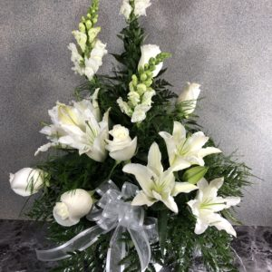 white lilies funeral arrangement in white urn vase