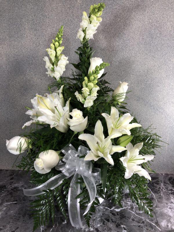 white lilies funeral arrangement in white urn vase